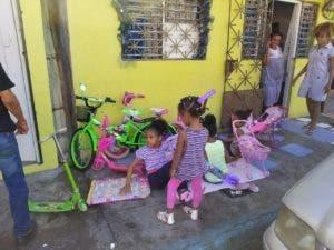 Niños disfrutan de sus juguetes frente a su hogar.