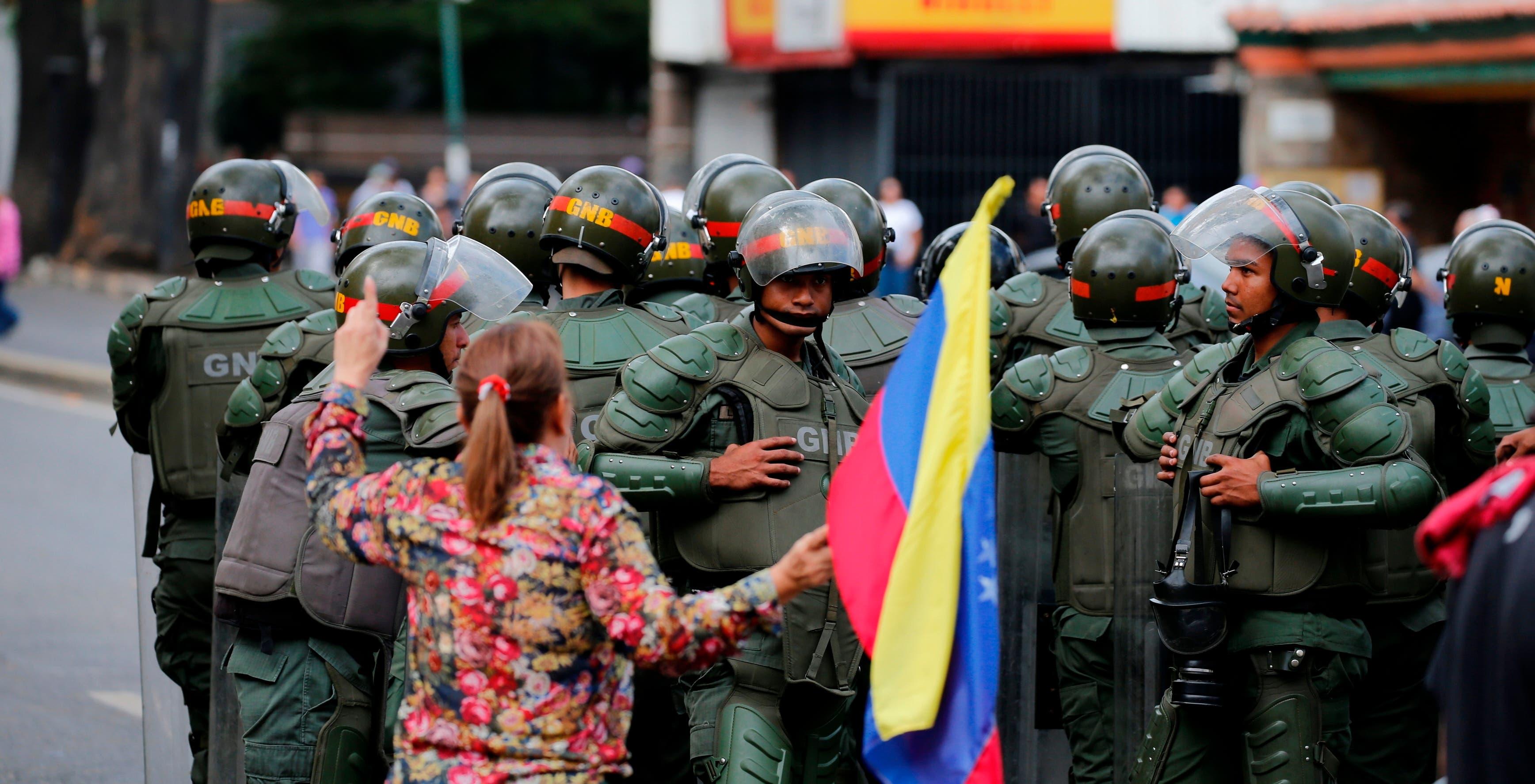5. Una mujer con una bandera nacional venezolana obstruye a los miembros de la Guardia Nacional Bolivariana bloqueando el paso de miembros de la oposición durante una marcha de protesta contra el presidente Nicolás Maduro en Caracas.