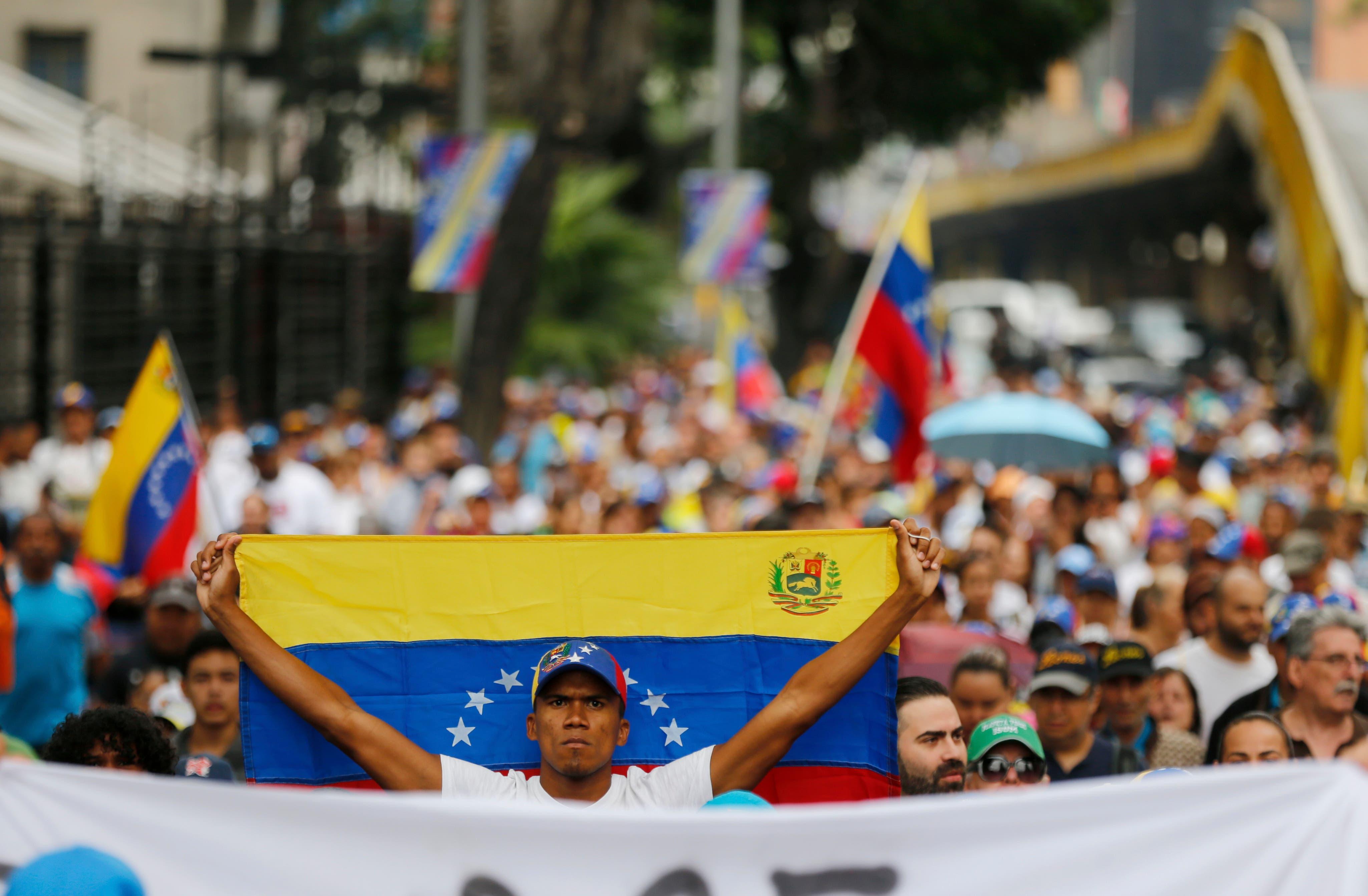 3. Un miembro de la oposición sostiene una bandera nacional venezolana durante una marcha de protesta contra el presidente Nicolás Maduro en Caracas, Venezuela.