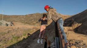 Un migrante hondureño pasa a una niña con su padre después de que brincaron la barda fronteriza para cruzar a San Diego, California, desde Tijuana, México, el jueves 3 de enero de 2019. (AP Foto/Daniel Ochoa de Olza)