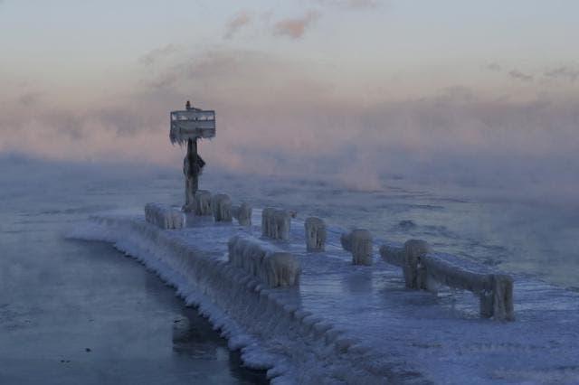 El faro de un puerto está cubierto por hielo y nieve sobre el lago Michigan en Chicago.