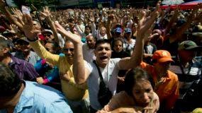"""Seguidores de la oposición corean """"Guaidó presidente"""" durante una sesión pública de la Asamblea Nacional en una calle de Caracas, Venezuela, el 11 de enero de 2019. Juan Guaidó, presidente de la asamblea controlada por la oposición, dice que, con el respaldo del país, está listo para asumir los poderes presidenciales de Nicolás Maduro y convocar nuevas elecciones. (AP Foto/Fernando Llano)"""