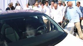 El presidente Medina, Rolando González y otros ejecutivos  prueban   un carro eléctrico.