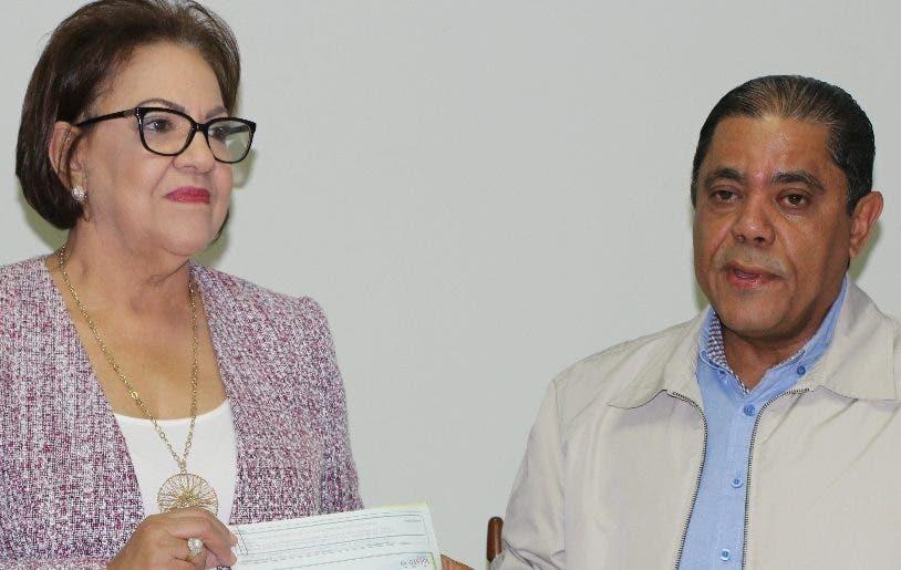 Marino Collante entregó cheque a Inmaculada Adames.