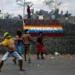 Manifestantes venezolanos lanzan piedras durante enfrentamientos con las autoridades en la frontera entre Venezuela y Brasil, el sábado 23 de febrero de 2019. Miles de personas permanecen en Pacaraima, en el cruce fronterizo internacional de la ciudad con Venezuela para exigir el ingreso de alimentos y medicinas. (AP Foto/Ivan Valencia)