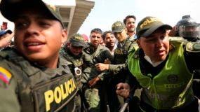 Policías de Colombia escoltan a un soldado de Venezuela que desertó en el puente internacional Simón Bolívar, donde los venezolanos intentaron introducir ayuda humanitaria al país pese a las objeciones del presidente, Nicolás Maduro, en Cúcuta, Colombia, el 23 de febrero de 2019. (AP Foto/Fernando Vergara)