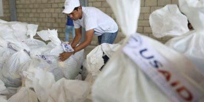 """Un voluntario organiza parte de los paquetes enviados por USAID como ayuda hunanitaria a Venezuela. El presidente Maduro rechazó la oferta de ayuda tras considera que """"un país no se desarrolla con migajas y mendicidad"""".(AP Photo/Fernando Vergara)"""
