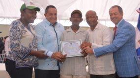 El director del IAD  entrega uno de los títulos provisionales a uno de  los beneficiados.
