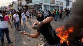 Un manifestante arroja piedras durante enfrentamientos con la Guardia Nacional Bolivariana en Ureña, Venezuela, cerca de la frontera con Colombia, el sábado 23 de febrero de 2019. (AP Foto/Rodrigo Abd)