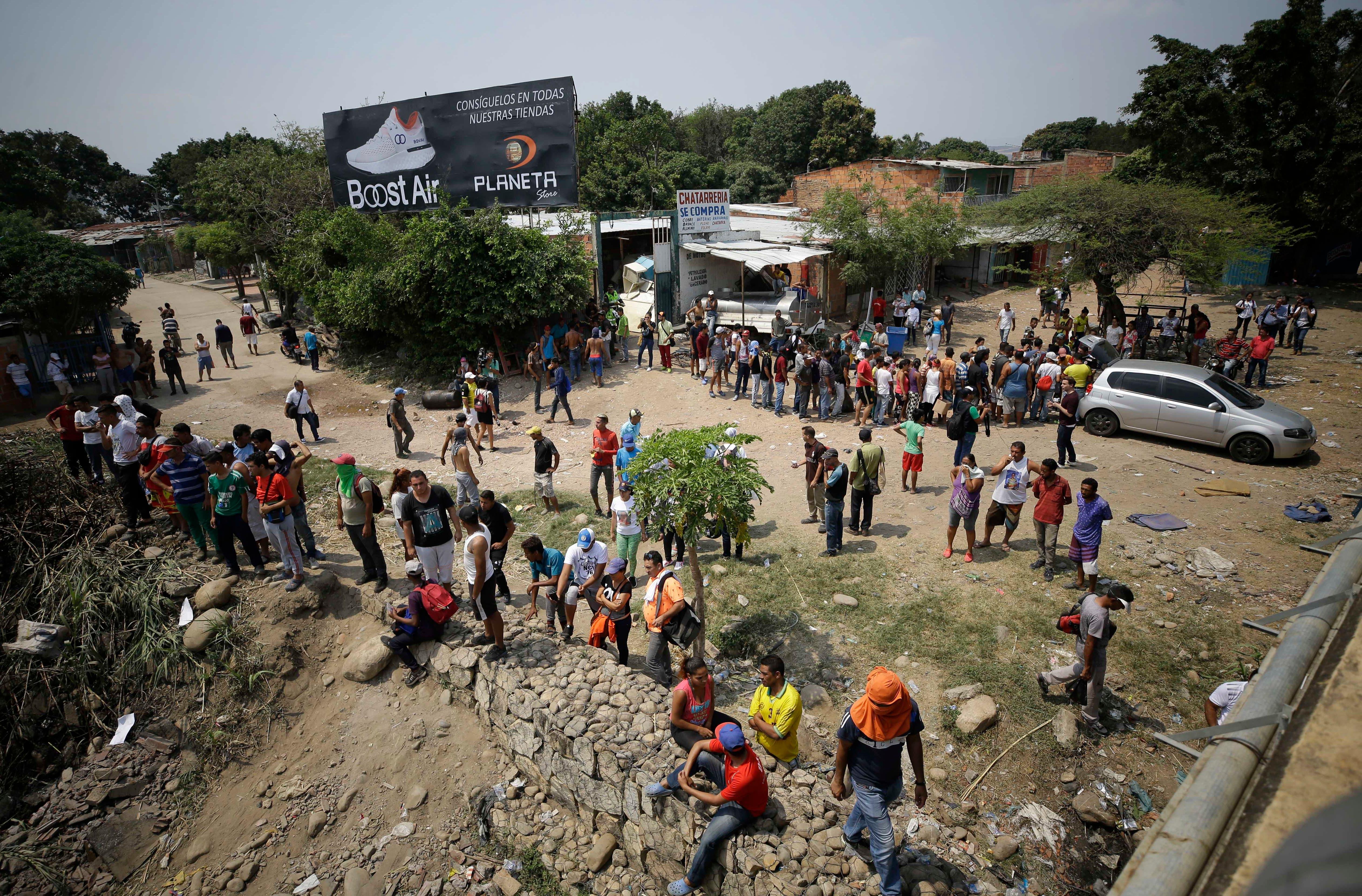 Los migrantes venezolanos esperan en la cola detrás de un vehículo para que los residentes colombianos entreguen comida gratis, mientras que otros, a continuación, observan cómo la gente trata de despejar una barricada creada por la Guardia Nacional de Venezuela en el Puente Internacional Simón Bolívar en La Parada, cerca de Cúcuta, Colombia. en la frontera con Venezuela, el domingo, 24 de febrero de 2019. AP