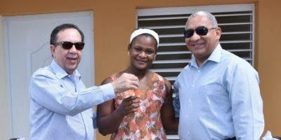 Crismery Santana recibe de manos de Héctor Valdez Albizu las llave de su nueva casa.