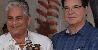 Llenas recibe una placa de Julio Brache, del Grupo Rica.