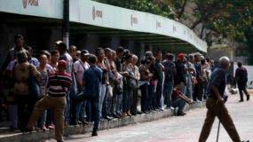 Gente aguarda transporte público en medio del apagón más prolongado y extendido de la historia de Venezuela, en Caracas, 8 de marzo de 2019. Para el sábado 9 de marzo de 2019 el servicio se había restaurado en algunas partes derl país, y en otras había apagones intermitentes. (AP Foto/Eduardo Verdugo)