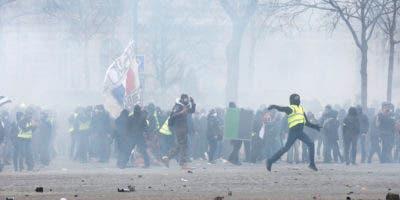Un manifestante de los chalecos amarillos arroja un objeto a la policía en París. (AP Foto/Christophe Ena)