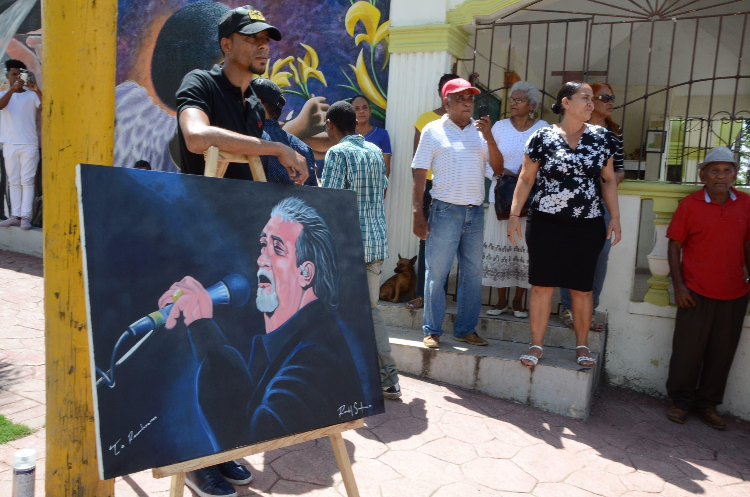 7. Un joven muestra una pintura con la imagen de Anthony Ríos durante entierro.