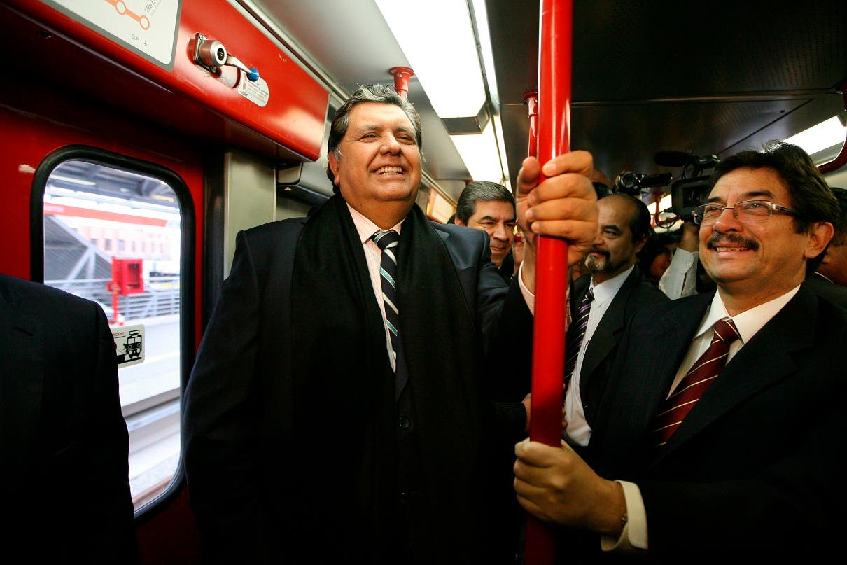 ARCHIVO - En esta foto de archivo del 11 de julio de 2011 el entonces presidente saliente de Perú, Alan García, a la izquierda, viaja en el sistema de tren eléctrico en Lima, Perú.  (AP Foto / Martín Mejía, Archivo)
