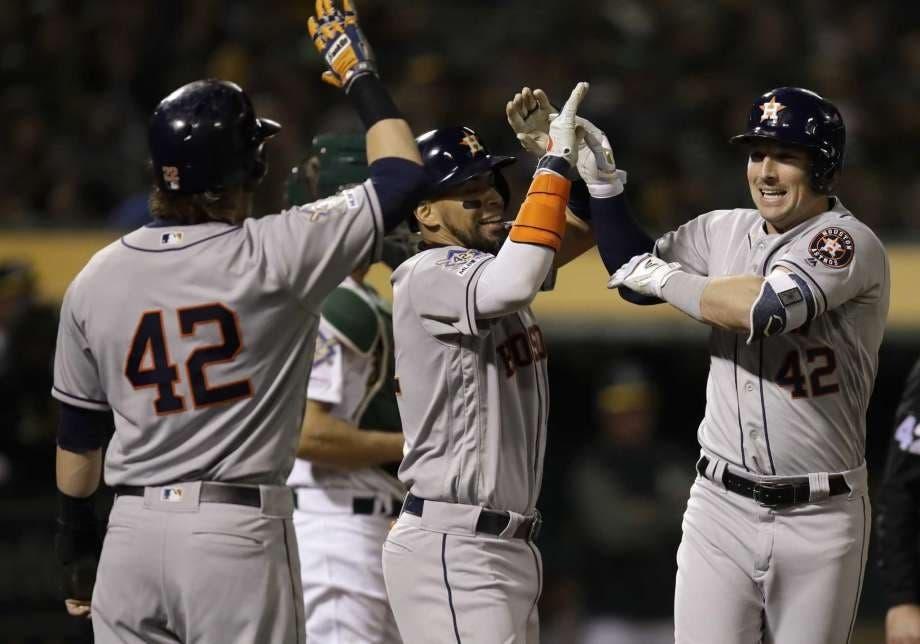 Alex Bregman es felicitado por compañeros del equipo tras conectar un jonrón con las bases llenas en la cuarta entrada.
