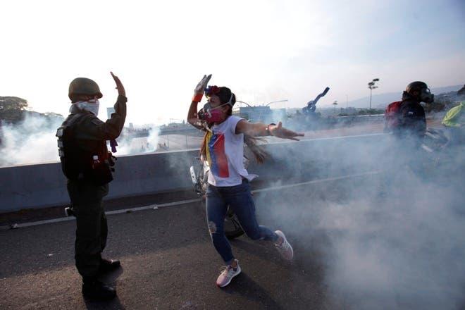 Un oponente al presidente de Venezuela, Nicolás Maduro, venció a un soldado rebelde en un paso elevado de la autopista fuera de la base aérea de La Carlota en medio de gas lacrimógeno disparado por soldados leales dentro de la base en CaracasAP