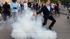 Un oponente del presidente de Venezuela, Nicolás Maduro, devuelve un recipiente de gas lacrimógeno a los soldados que lo lanzaron a un pequeño grupo de civiles y tropas rebeldes reunidas fuera de la base aérea de La Carlota en Caracas, Venezuela