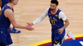Nikola Jokic (izquierda), pívot de los Nuggets de Denver, felicita a su compañero Jamal Murray, quien encestó ante los Spurs de San Antonio en el quinto partido de su serie de playoffs, el martes 23 de abril de 2019 (AP Foto/David Zalubowski)