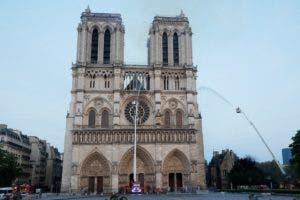 Los miembros de la brigada de bomberos de París rocían agua sobre la fachada de la catedral de Notre Dame