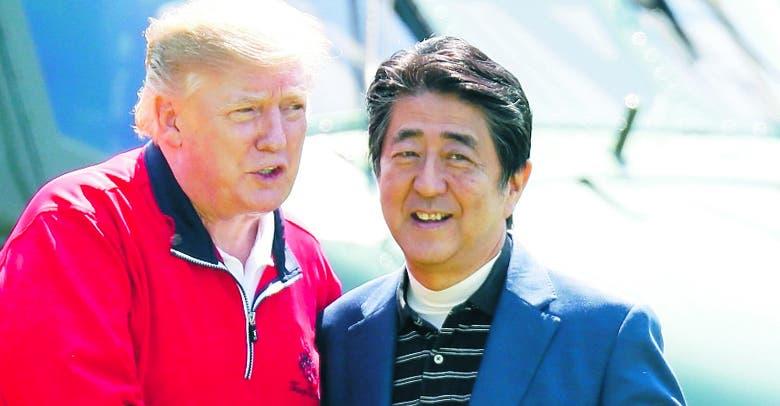 Donald Trump habla  con el primer ministro Shinzo Abe.