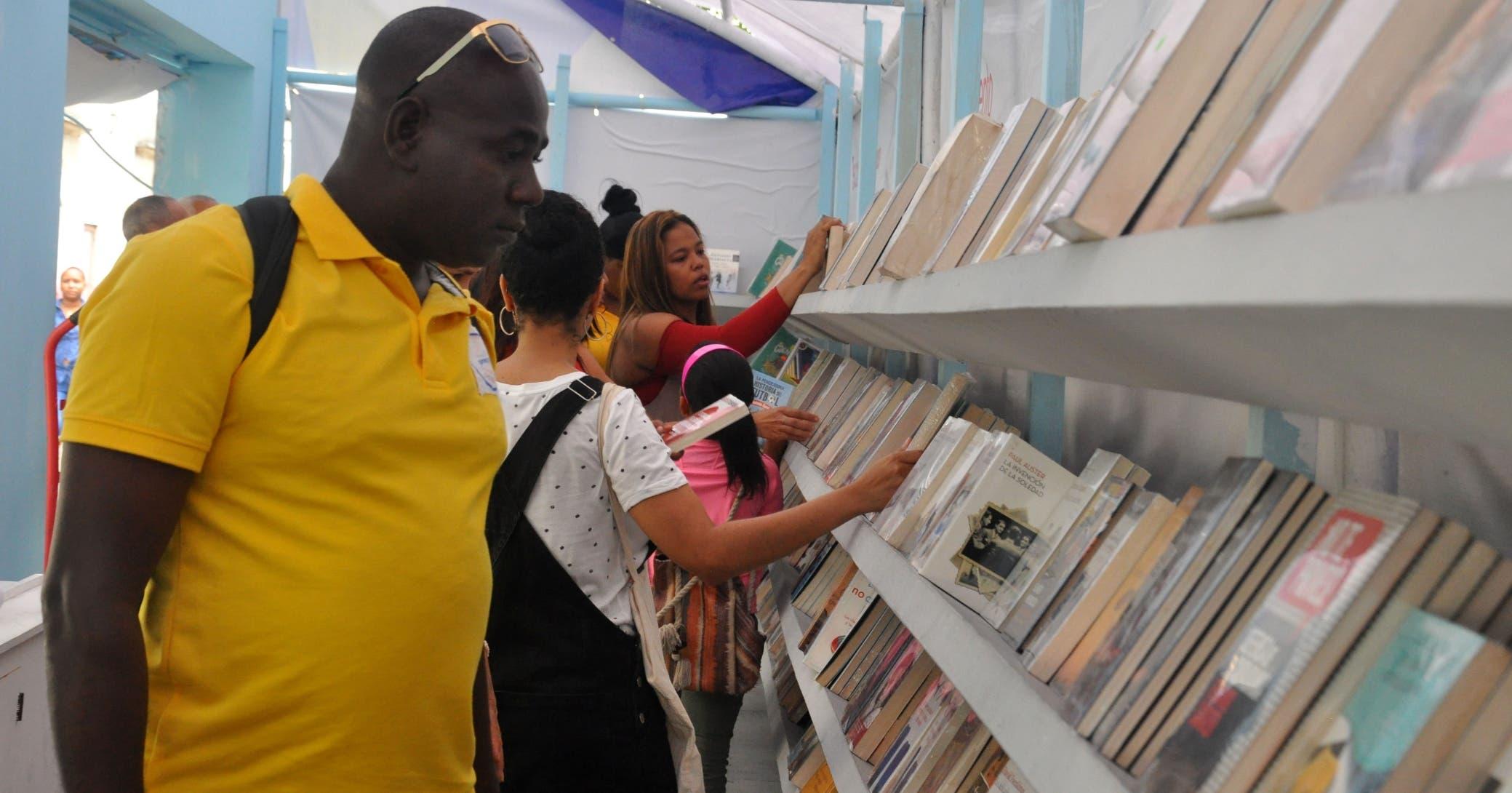 Asistentes a la Feria del Libro escogen entre varios títulos expuestos en una de las librerías que participaron en la fiesta cultural.  Caroline Fernández
