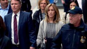 La actriz Felicity Huffman, centro, sale de una corte federal con su hermano Moore Huffman Jr., izquierda,  en Boston, donde la estrella se declaró culpable de participar en un ardid de sobornos para admisiones universitarias.
