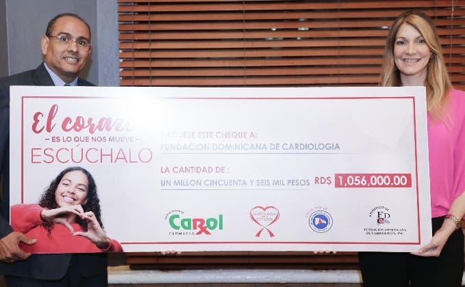 Osiris Valdez recibe el cheque de manos de María Teresa Ferreiro.