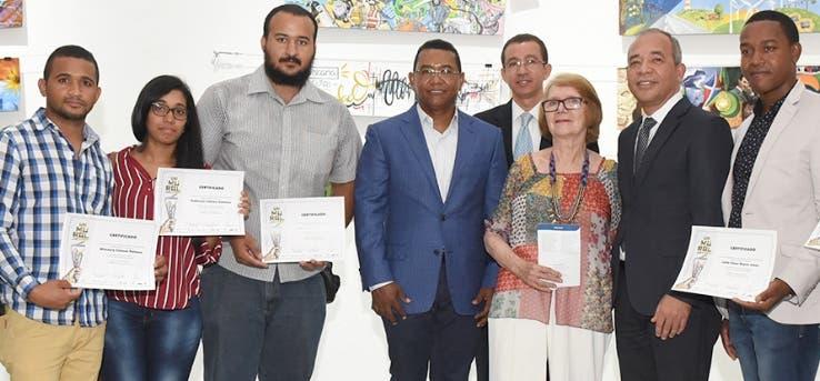 Los ganadores  reciben sus certificados de manos de los directivos de ambas entidades.