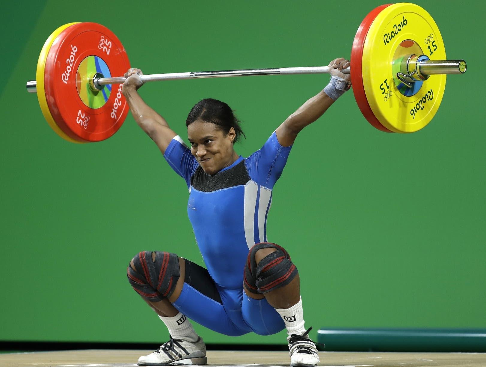 Yuderqui Contreras ejecuta un movimiento durante su brillante carrera en un evento de pesas.