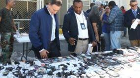 El procurador Jean Rodríguez observa los celulares y objetos decomisados.  fuente externa