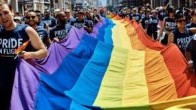 ARCHIVO - En esta fotografía del 24 de junio de 2018, unas personas llevan una bandera de la comunidad LGBTQ en la Quinta Avenida de la ciudad de Nueva York durante el desfile del Orgullo Gay. (AP Foto/Andres Kudacki, Archivo)