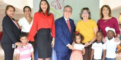 Ejecutivos de ambas entidades junto a niños que serán beneficiados.