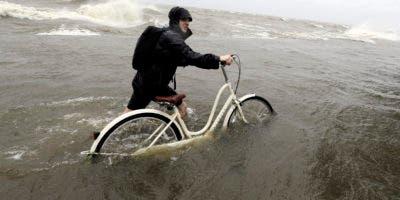 Tyler Holland guía su bicicleta mientras el viento de la tormenta tropicla Barry empuja el agua del lago Pontchartrain sobre el dique el sábado 13 de julio de 2019 en Mandeville, Luisiana. (AP Foto/David J. Phillip)