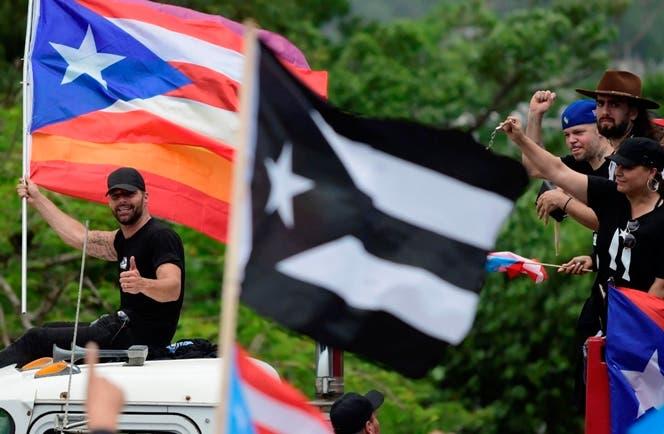 Ricky Martin, con una bandera puertorriqueña y una pancarta en forma de arco iris, muestra un pulgar hacia arriba cuando se une a miles de puertorriqueños por lo que muchos esperan ser una de las protestas más grandes que se hayan visto en el territorio de los EE. UU. expulsar al gobernador Ricardo Rossello de su oficina, en San Juan, Puerto Rico, el lunes 22 de julio de 2019. AP.