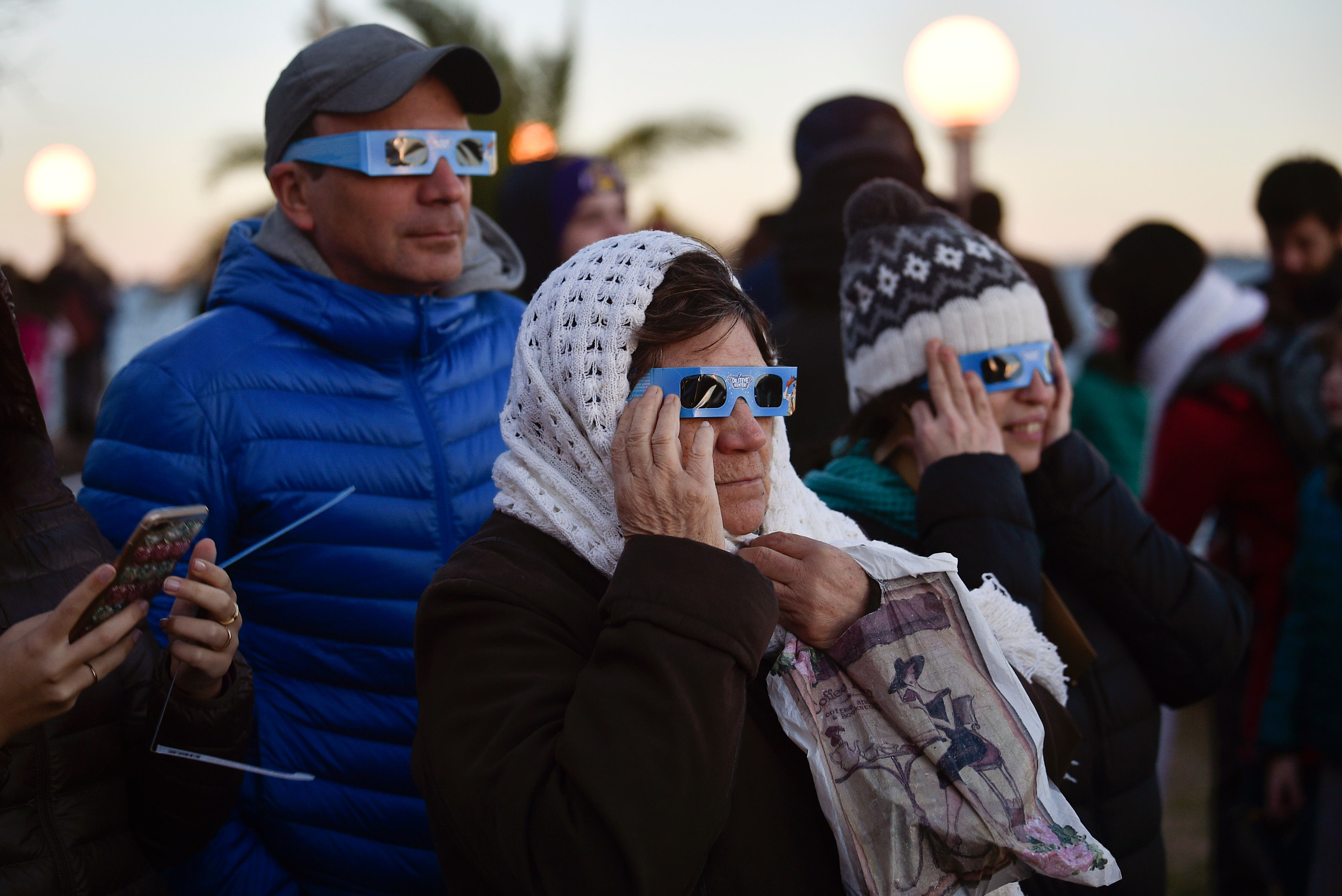 5. Personas observan el eclipse solar en Chascomus, Argentina.AP
