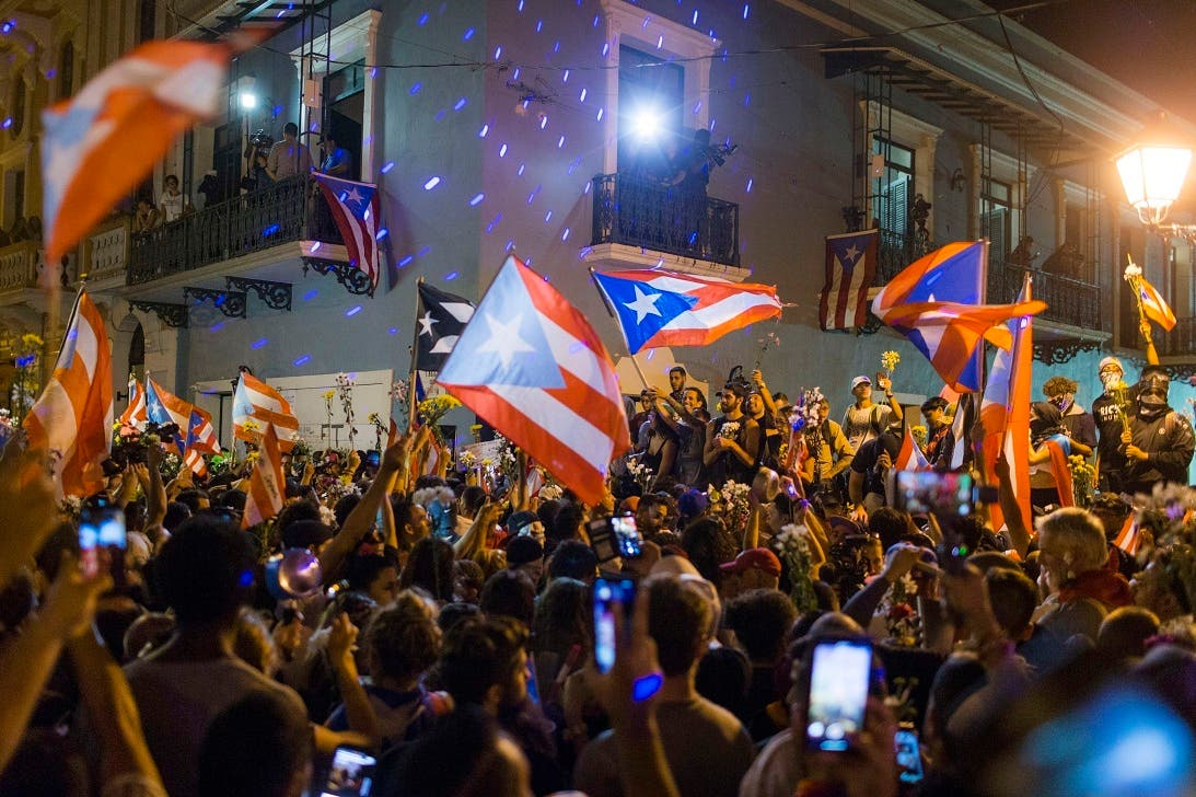 3. Gente celebrando ante la residencia oficial del gobernador de Puerto Rico, La Fortaleza, después de que el gobernador, Ricardo Rosselló, anunciara que dimitirá el 2 de agosto tras casi dos semanas de protestas, en San Juan, Puerto Rico, el jueves 25 de julio de 2019. (AP Foto/Dennis M. Rivera Pichardo)