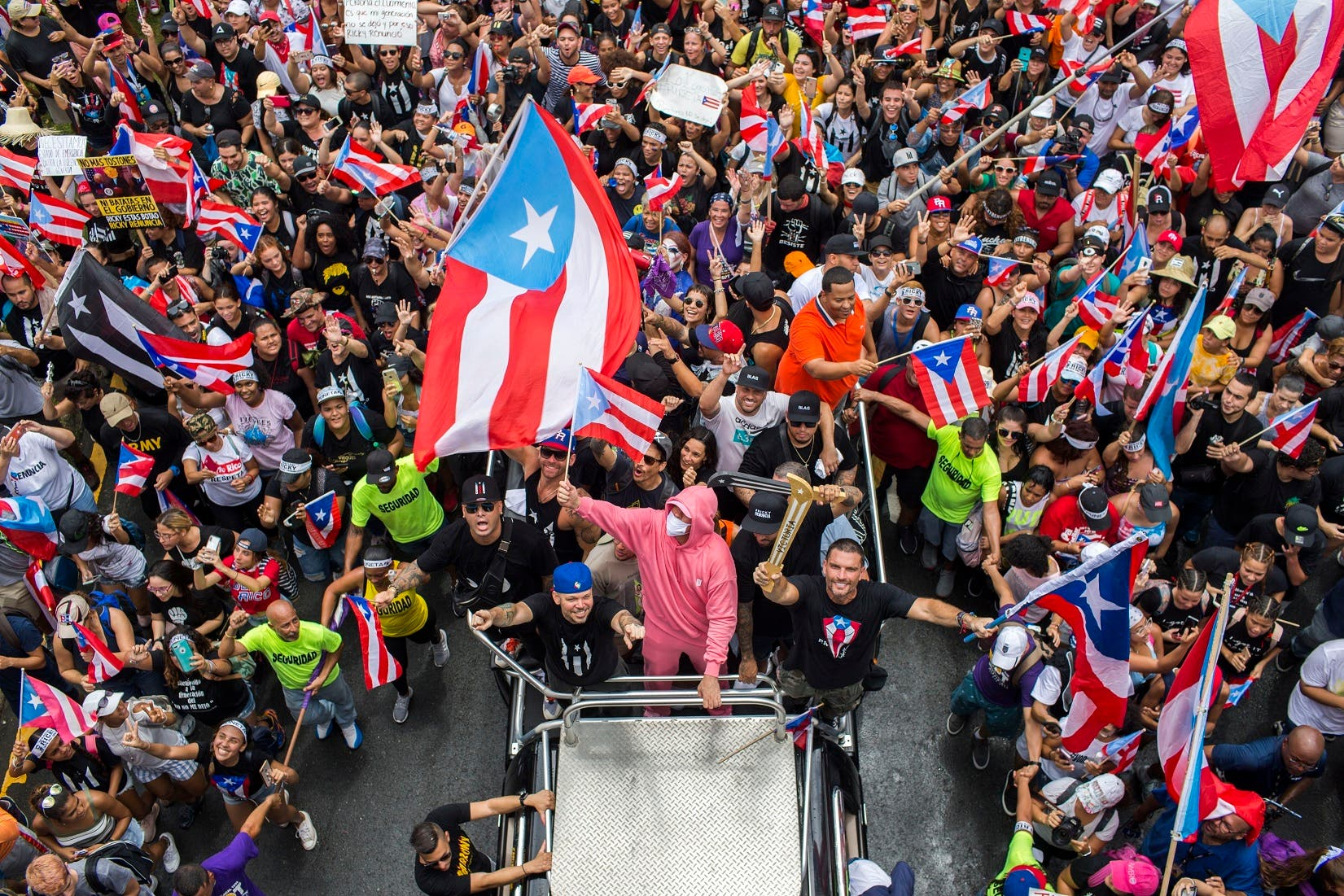 """1. Wisin, Residente, Bad Bunny, Nicky Jam y Julián Gil desde un vehículo, participando de la marcha """"Somos más""""."""