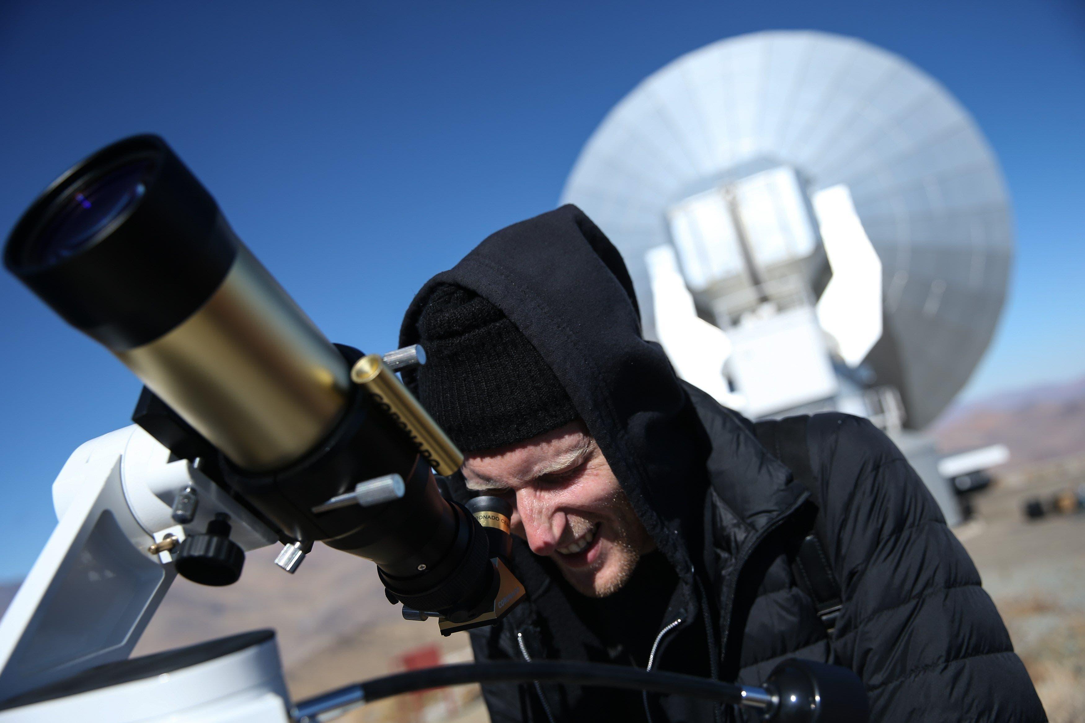 2. Un hombre observa el sol a través de un telescopio horas antes de que comience el eclipse solar total, este martes en el Observatorio de La Silla, situado en la región de Coquimbo (Chile). Cientos de personas se reunieron hoy para presenciar el eclipse total y parcial de sol que se pudo ver desde distintos países de América. EFE/ Alberto Valdés