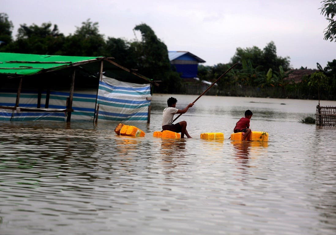 Dos hombres navegan en un mercado inundado por las lluvias de los últimos días en Myanmar.EFE/EPA/NYUNT WIN.