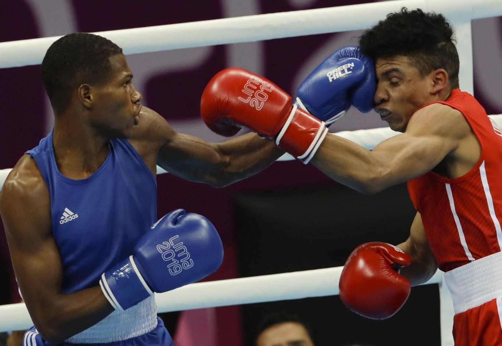 Rodrigo Marte, izquierda, intercambia golpes con el cubano Yosbany Veitia  durante le pelea por el oro en Lima.