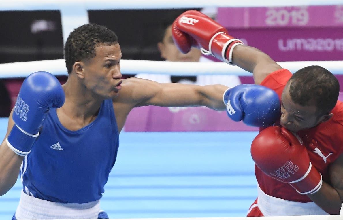 Leonel de los Santos  castiga al cubano Lázaro Álvarez en pelea por el oro  .  Manolito Jiménez