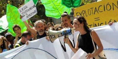 """Centenares de jóvenes de Fridays for Future y XR Bcn se han manifestado este viernes ante el consulado de Brasil en Barcelona , para protestar por los incendios que están devastando la selva del Amazonas y que avanzan a una velocidad que califican de """"alarmante"""".EFE/ Quique García."""