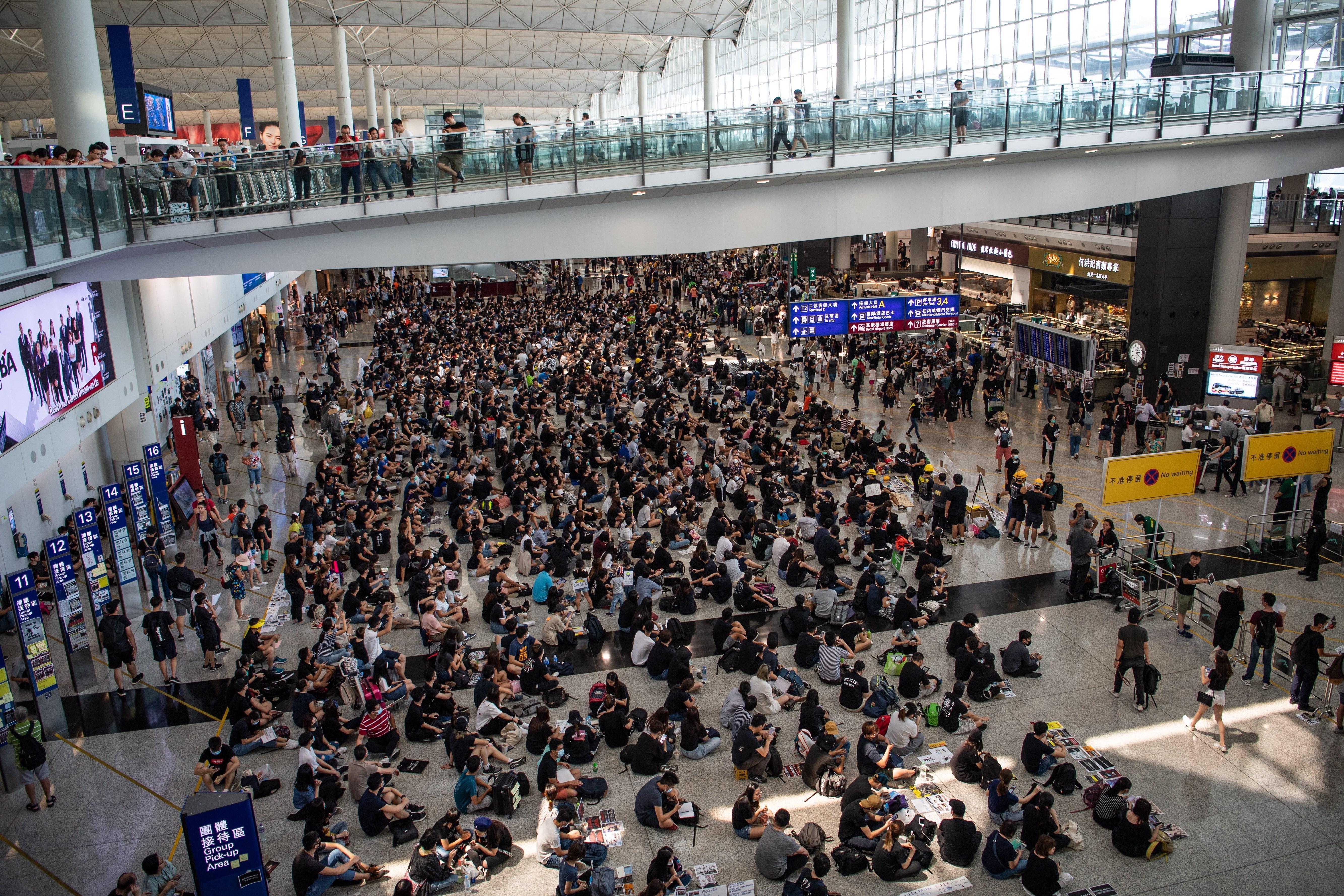 """Cientos de manifestantes hongkoneses realizan una sentada en el Aeropuerto Internacional de Hong Kong en protesta contra la violencia policial y el gobierno chino, este martes, en Hong Kong (China). Los pasajeros se enfrentan a la segunda jornada de parálisis por la protesta masiva de los civiles al tiempo que la jefa del Ejecutivo, Carrie Lam, ha advertido de que los acontecimientos están llevando a la ciudad a un """"callejón sin salida"""". EFE."""