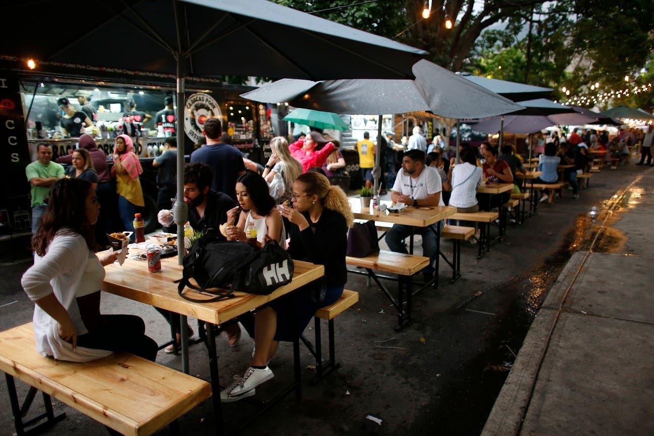 Gente comiendo en mesas de picnic colocadas ante camionetas restaurante en Caracas, Venezuela, el sábado 3 de agosto de 2019. (AP Foto/Ariana Cubillos)