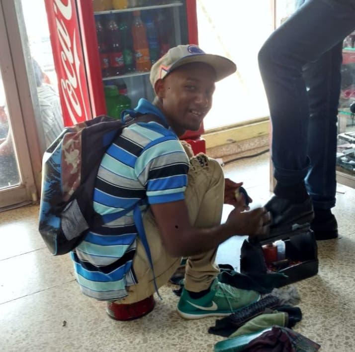 Luis Alejandro en plena labor. Después de limpiar zapato va a coger clases en la UASD.