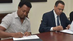 Pedro Martínez y el ministro de Educación, Antonio Peña Mirabal, firman el acuerdo.
