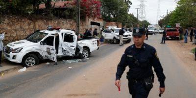 Un oficial de policía camina cerca del auto acribillado a balazos conducido por el jefe de policía Felix Ferrari, quien murió en un tiroteo cuando el narcotraficante encarcelado Jorge Teófilo Samudio González escapó de la custodia, en Asunción, Paraguay, el miércoles 11 de septiembre de 2019.  (AP Foto / Jorge Sáenz)