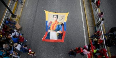 En esta imagen, tomada el 12 de septiembre de 2019, partidarios del presidente de Venezuela, Nicolás Maduro, despliegan una pancarta con la imagen del héroe independentista Simón Bolívar durante una marcha para conmemorar el 11mo aniversario de las juventudes del Partido Socialista, en Caracas, Venezuela. (AP Foto/Ariana Cubillos)